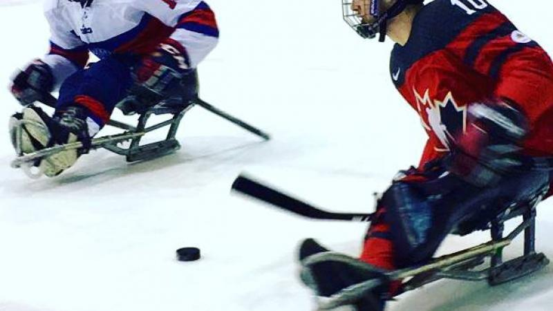 Two Para ice hockey players duel on the ice