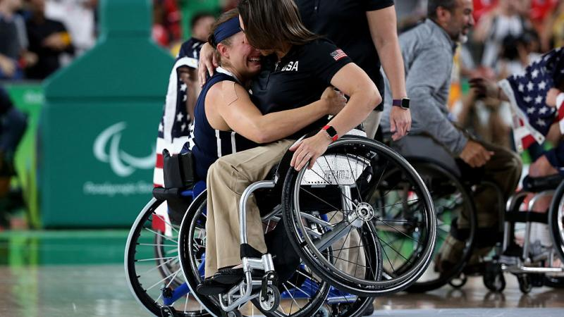 Two women in wheelchairs hugging each other