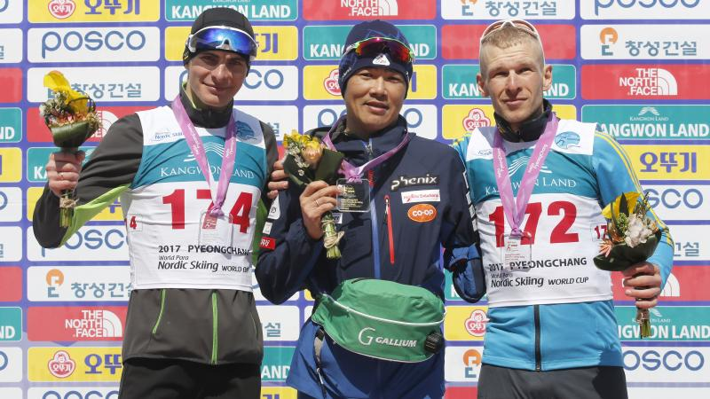 Three men on a podium, holding flower bouquets