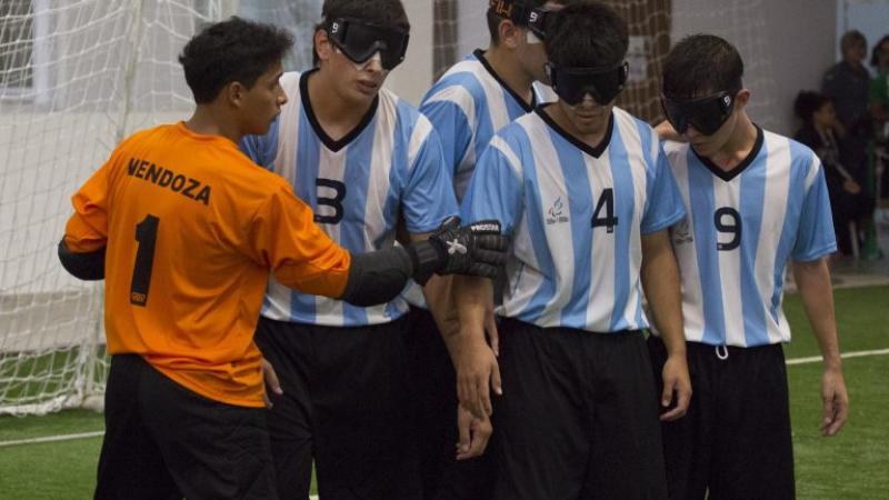 A blind football team organise themselves on the pitch