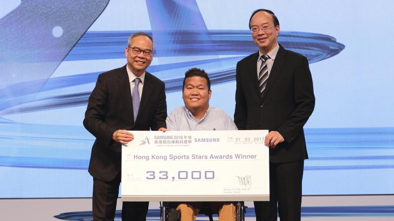 Man in middle in wheelchair holds giant check with two other men standing