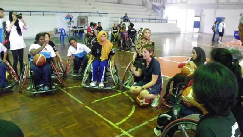 A coach kneels while women in wheelchairs gather around her