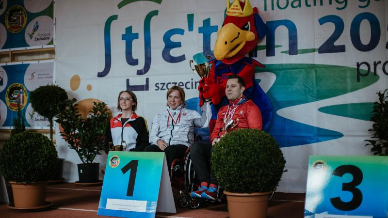 Three shooters on a podium with event mascot