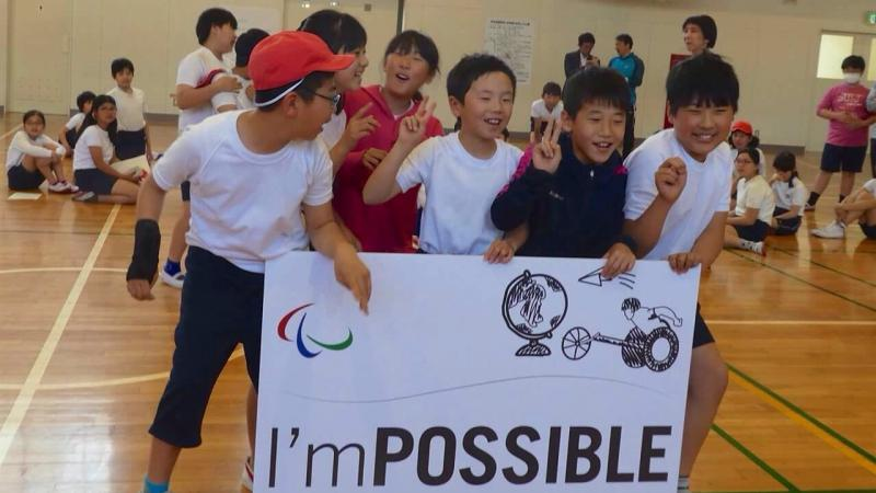 Group of Japanese kids holding up a sign