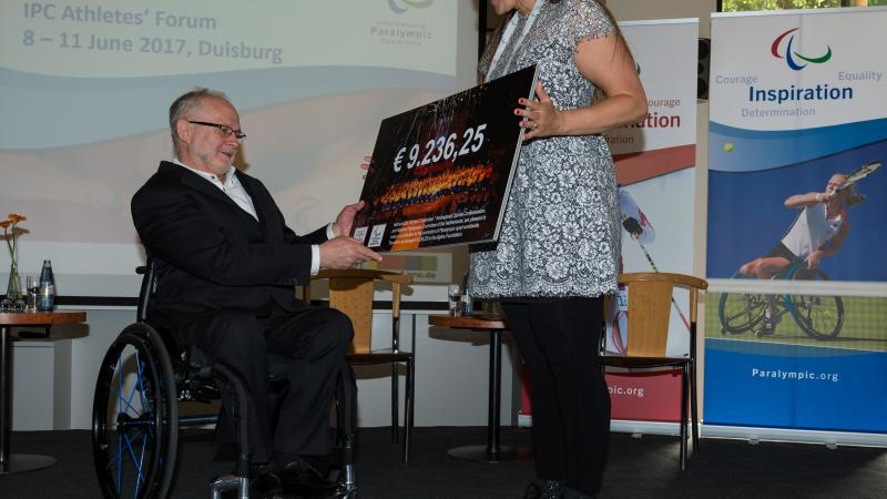 Woman presents man in wheelchair with a cheque