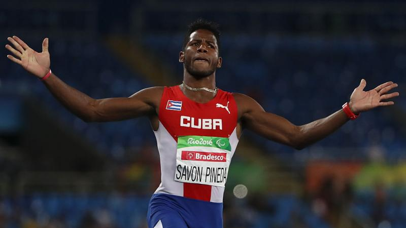 male sprinter crosses finish line with arms outstretched