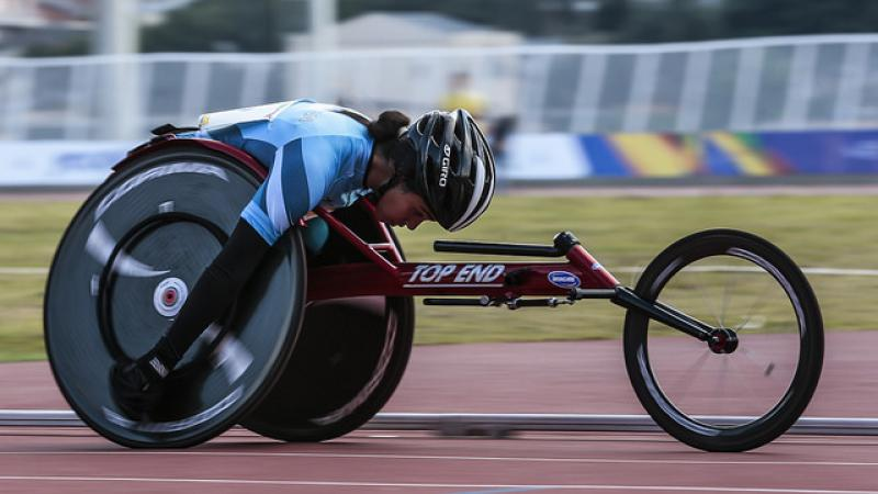 female wheelchair racer on track with head down