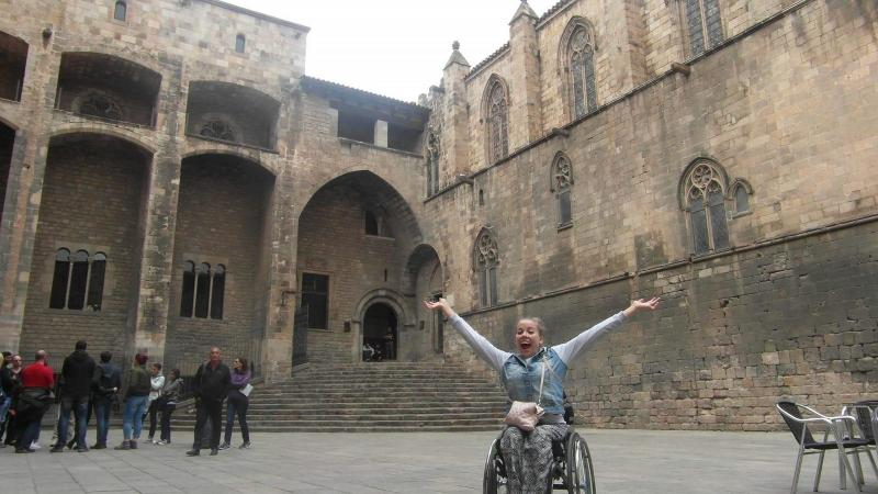 woman in wheelchair smiling with arms outstretched