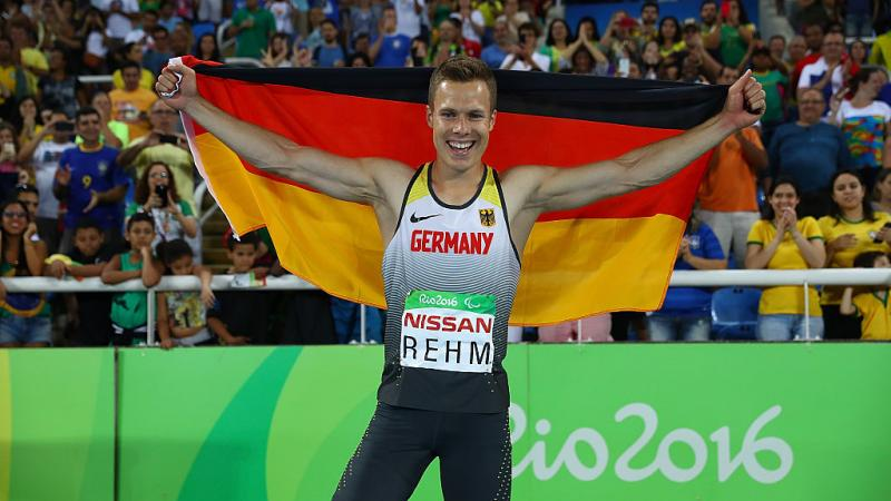 Man holds up German flag and smiles