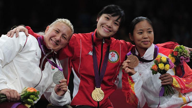 three women with medals standing on a podium