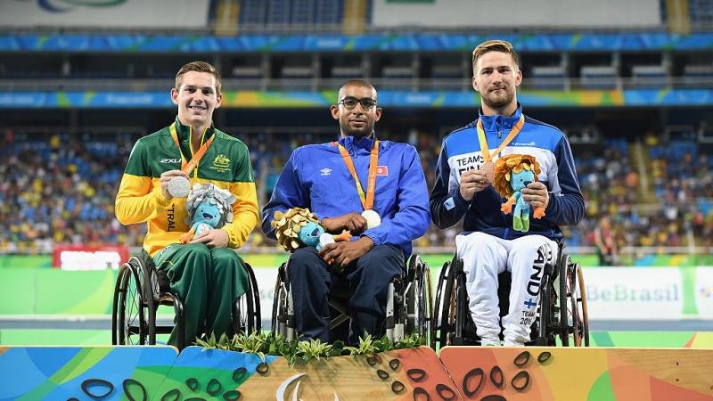 three men in wheelchairs smile holding their medals on the podium