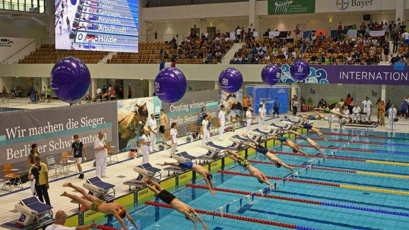 a group of male para swimmers dive into the pool