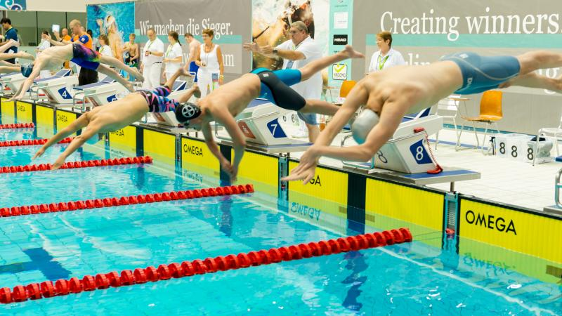 a group of male swimmers dive into the pool at the start of the race