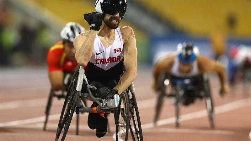 a wheelchair racer pumps his fist after crossing the line