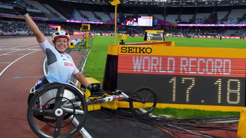 Woman in racing wheelchair next to a screen