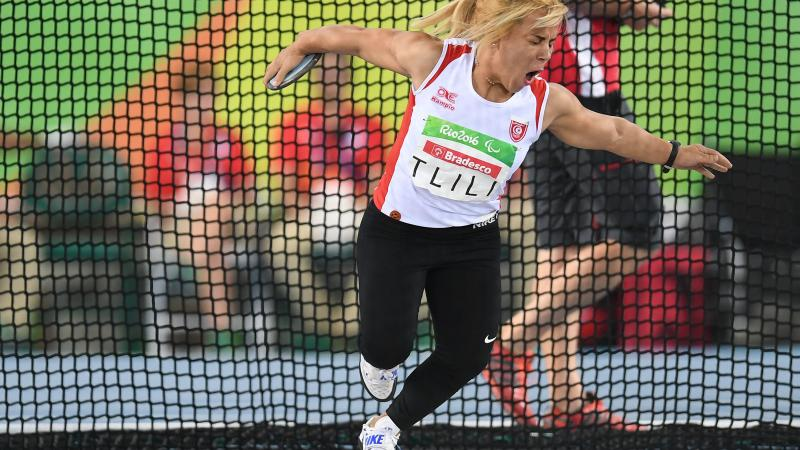 A woman in white vest and black bottoms pulls a face as she gets ready to throw a discus.