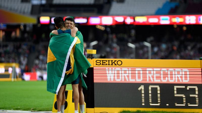 Two athletes hug on the track in front of a bulletin board showing 'WR'