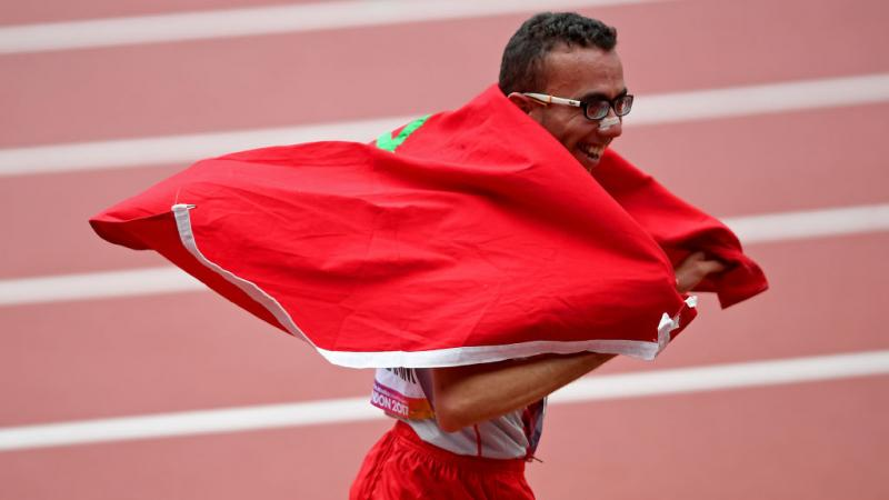 Man in running clothes celebrates with Morocco flag