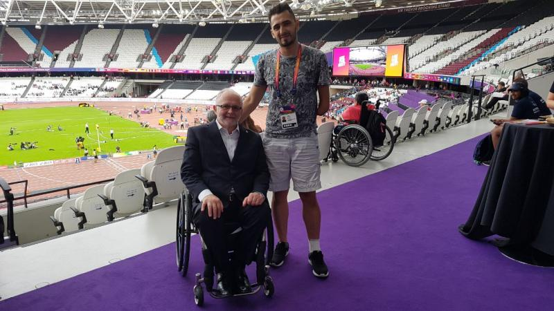a para athlete stands beside a man in a wheelchair