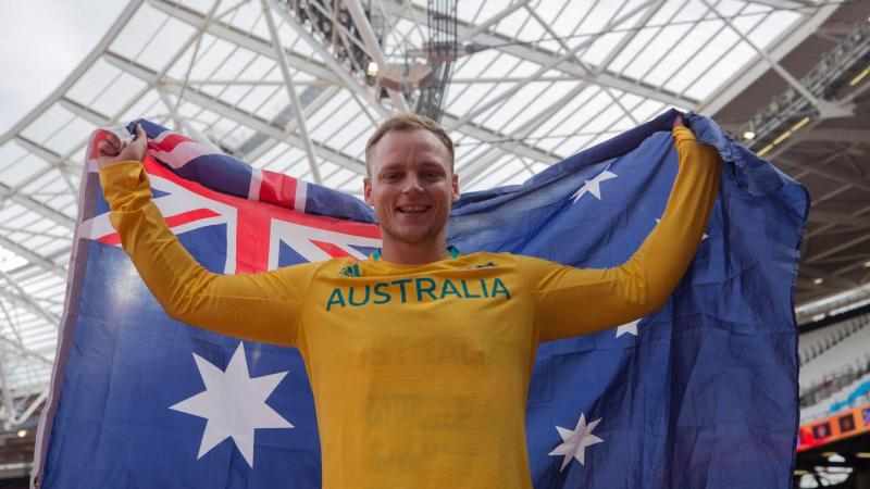 An athlete poses with the Australia flag after winning gold