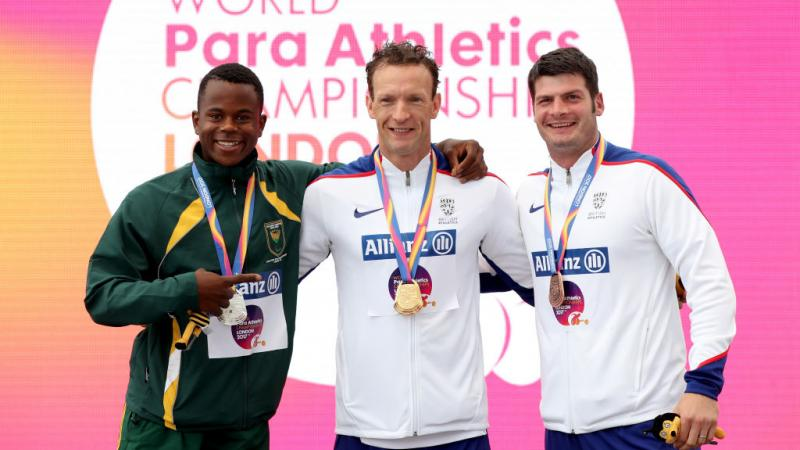 three men stand on the podium with their medals