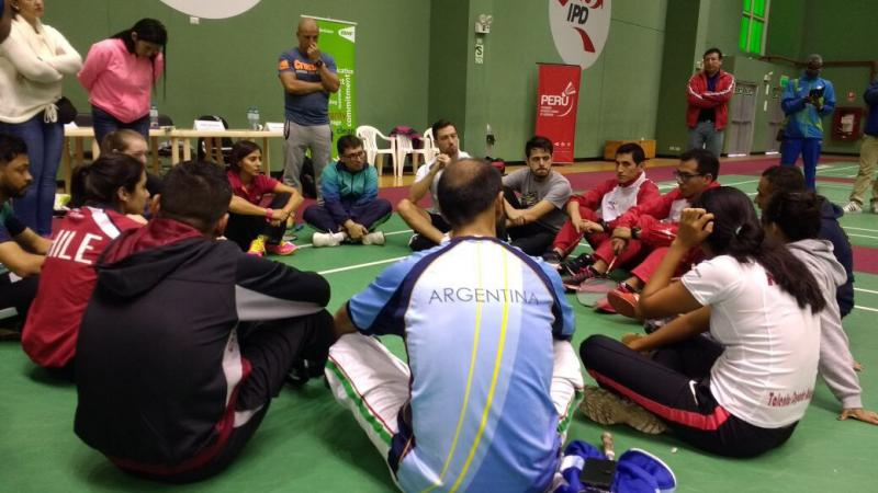 a group of para athletes sit having a group discussion