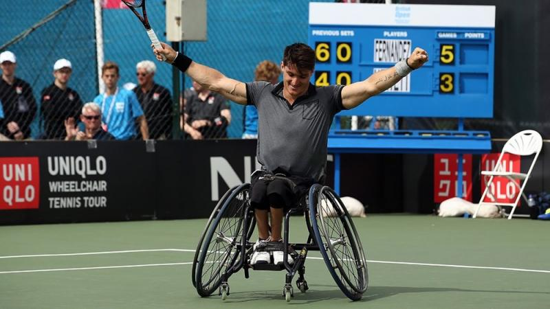 a wheelchair tennis player raises his arms in celebration