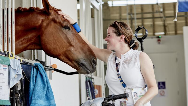 a para equestrian rider pats her horse in the stables
