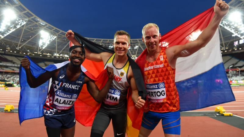 three men celebrate with the flags of their countries