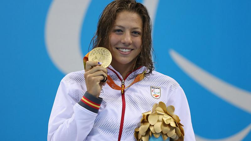 a female Para swimmer holds up her gold medal