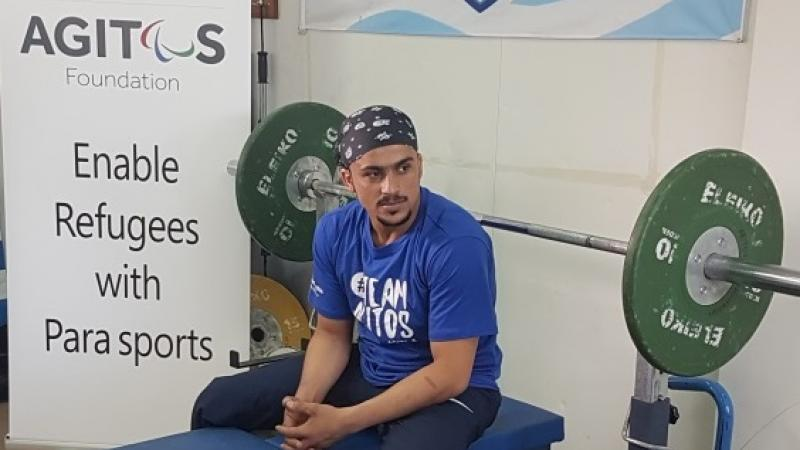 a male Para powerlifter sits on his bench