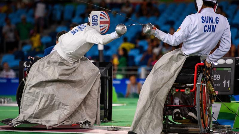 two wheelchair fencers mid bout