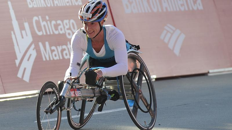 a female wheelchair racer celebrates crossing the line