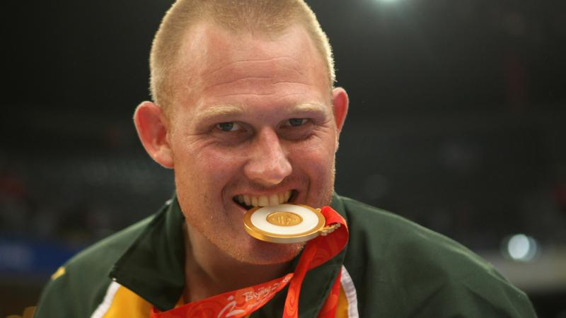 a male Para athlete bites his medal