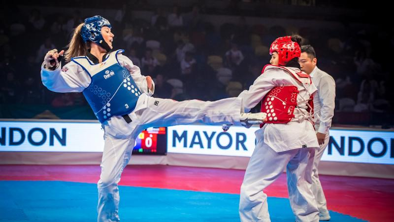 two female Para taekwondo fighters kick at each other