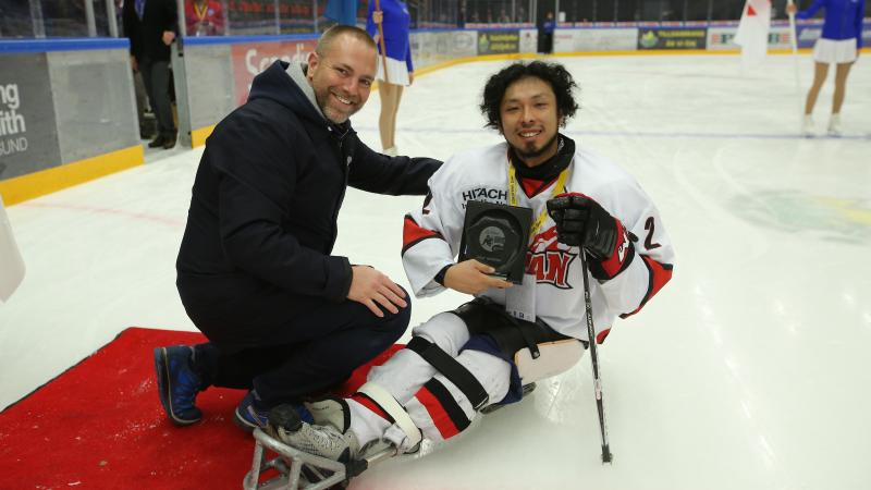 a male Para ice hockey player smiles after being presented with an award