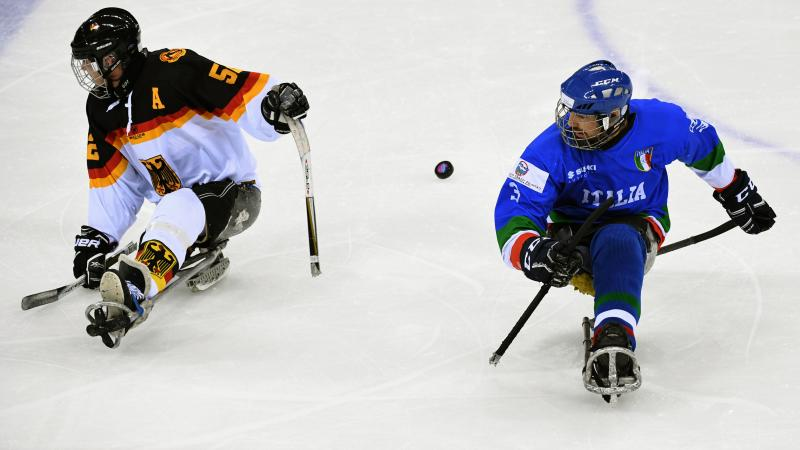 two male Para ice hockey players contest a puck