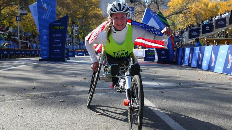 a female Para wheelchair racer celebrates with an American flag