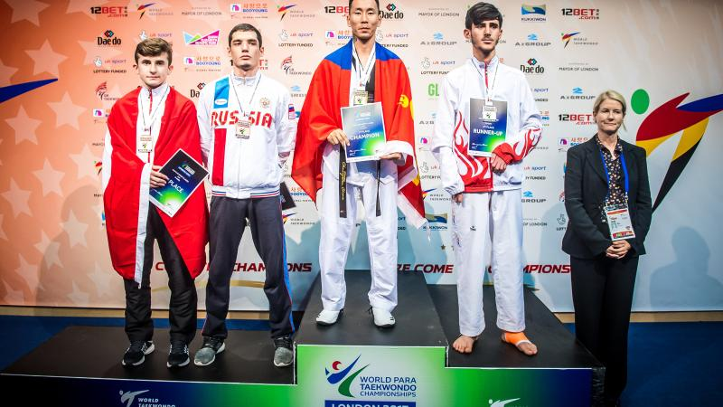 a group of Para taekwondo fighters stand on the podium