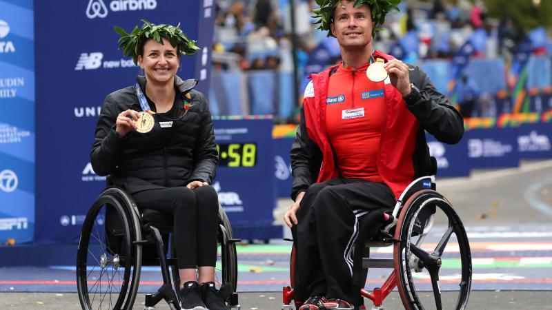 a male and female wheelchair racer celebrate with their gold medals