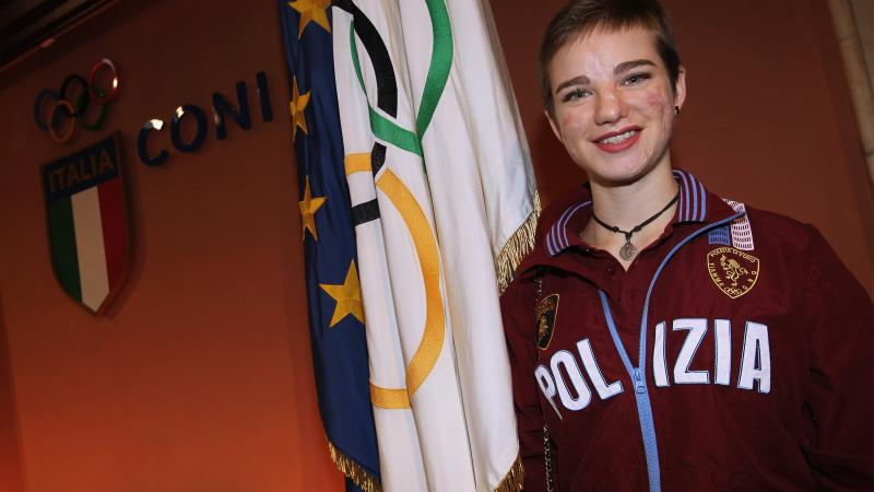 an female Para athlete smiles in front of an Italian flag