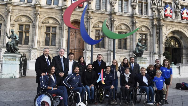 Group of people smiling in front of the Agitos logo and the municipality of Paris