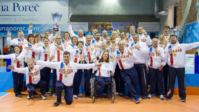 a group of male and female sitting volleyball players celebrate