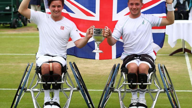 two male wheelchair tennis players hold their trophy and the British flag