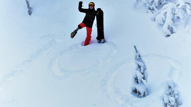 a male Para snowboarder stands on a '100' drawn in the snow