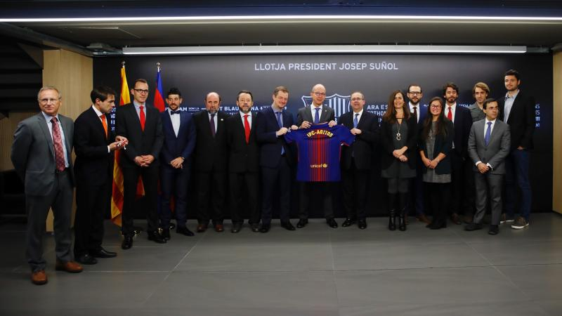 a group of men and women stand holding a Barcelona shirt
