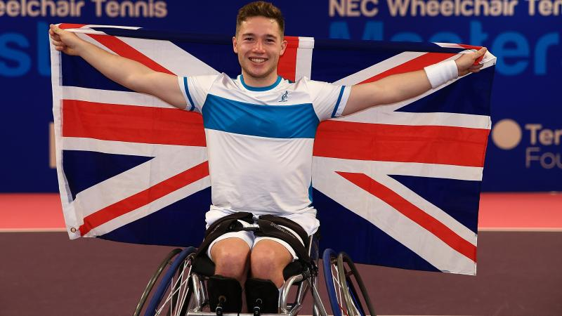 a male wheelchair tennis player holds up the Union Jack