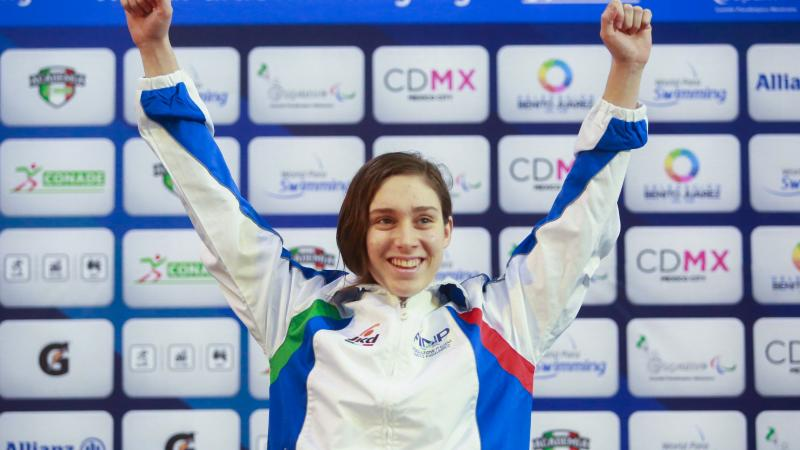 a female Para swimmer raises her arms on the podium