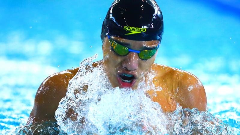 a male Para swimmer takes a breath out of the water between strokes