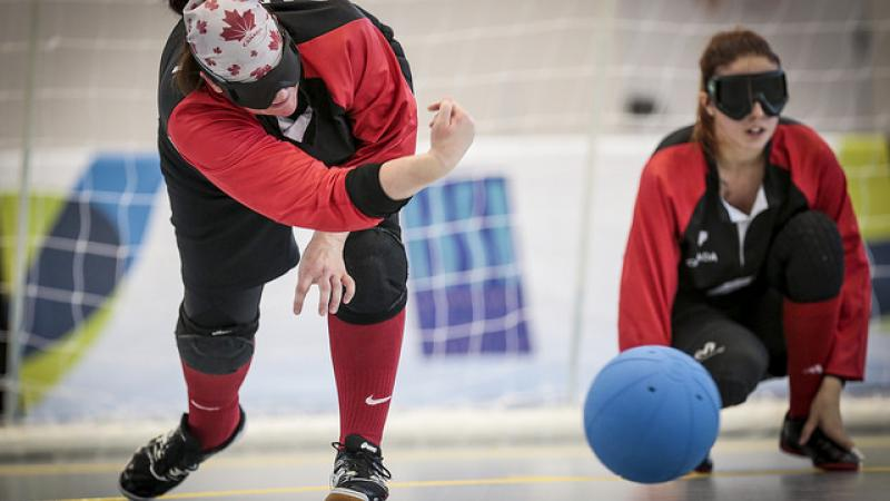 Woman goalball player rolls a ball